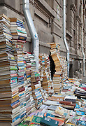 Piles of book stacked againt Bucharest Univerity Building, Secondhand bookseller, University Square, Bucharest