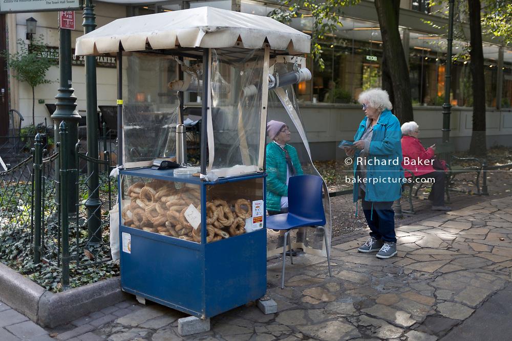 A Polish lady street kiosk snack seller talks to another woman,  on 23rd September 2019, in Krakow, Malopolska, Poland.