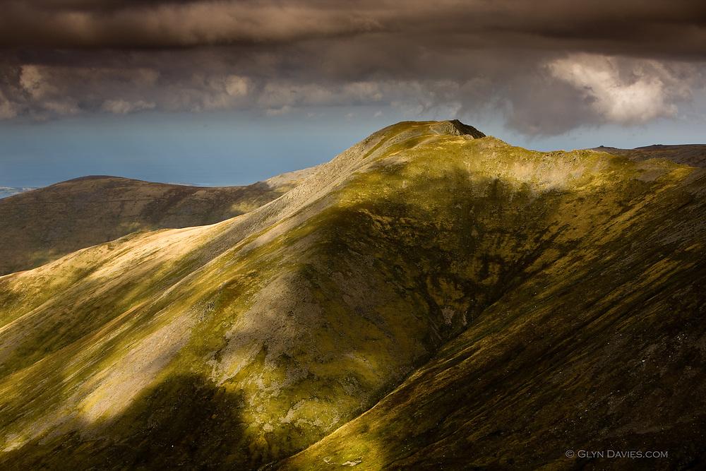 The peak of Yr Elen in the Carneddau range, Snowdonia, covered in shadows of passing cumulus clouds.
