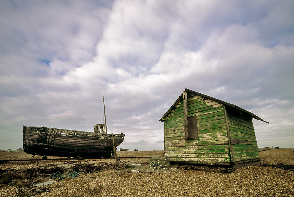 An old fishing boat and shack on the sands at Dungeness. Kent UK February 2005
