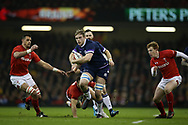 Jonny Gray of Scotland © makes a break past Aaron Shingler (l) , Gareth Davies and Rhys Patchell of Wales ® and heads towards the try line within the 1st few minutes of the match.  Wales v Scotland, NatWest 6 nations 2018 championship match at the Principality Stadium in Cardiff , South Wales on Saturday 3rd February 2018.<br /> pic by Andrew Orchard, Andrew Orchard sports photography
