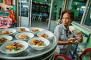 "11 JANUARY 2013 - BANGKOK, THAILAND:    A Muslim woman packages community lunches to be eaten after noon prayers at a Mosque in the Ban Krua neighborhood in Bangkok. The Ban Krua neighborhood of Bangkok is the oldest Muslim community in Bangkok. Ban Krua was originally settled by Cham Muslims from Cambodia and Vietnam who fought on the side of the Thai King Rama I. They were given a royal grant of land east of what was then the Thai capitol at the end of the 18th century in return for their military service. The Cham Muslims were originally weavers and what is known as ""Thai Silk"" was developed by the people in Ban Krua. Several families in the neighborhood still weave in their homes.                 PHOTO BY JACK KURTZ"
