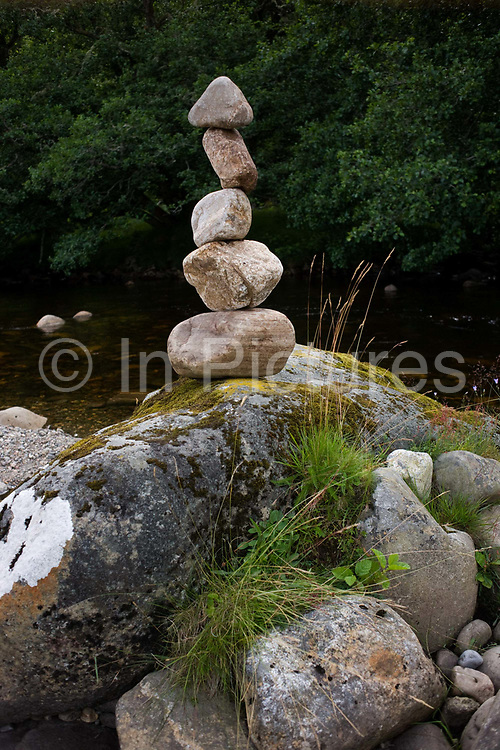 Piled river bed stones on the River Calder in Glen Bauchor, Newtonmore, Scotland. An artist has spent many hours in this tranquil place, sourcing and selecting the right stones to pile up vertically on top of each other. Rock balancing can be a performance art, a spectacle, or devotion, depending upon the interpretation by its audience. Essentially, it involves placing some combination of rock or stone in arrangements that require patience and sensitivity to generate, and which appear to be physically impossible while actually being only highly improbable.
