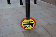 A building site Banksmans lollipop sign that usually tells road-users to allow for turning construction traffic, is tied upside down on to a post in the street on Sun Street near Liverpool Street Station in the City of London, the capitals financial district - aka the Square Mile, on 8th August, in London, England.