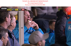 TV OUT. ALL BROADCAST WEBSITES OUT. No cropping permitted. Picture must be credited to BBC. We are advised that videograbs should not be used more than 48 hours after the time of original transmission, without the consent of the copyright holder Screen Grab of Sutton's reserve goalkeeper Wayne Shaw eating a pie on the touchline during the Emirates FA Cup, Fifth Round match at Gander Green Lane, London.