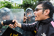 24 MAY 2014 - BANGKOK, THAILAND: A anti-coup protestor reaches out to shake hands with police at a police roadblock in Bangkok. There were several marches in different parts of Bangkok to protest the coup that unseated the popularly elected government. Soldiers and police confronted protestors and made several arrests but most of the protests were peaceful. The military junta also announced that firing of several police commanders and dissolution of the Thai Senate. The junta also changed its name from National Peace and Order Maintaining Council (NPOMC) to the National Council for Peace and Order (NCPO).   PHOTO BY JACK KURTZ