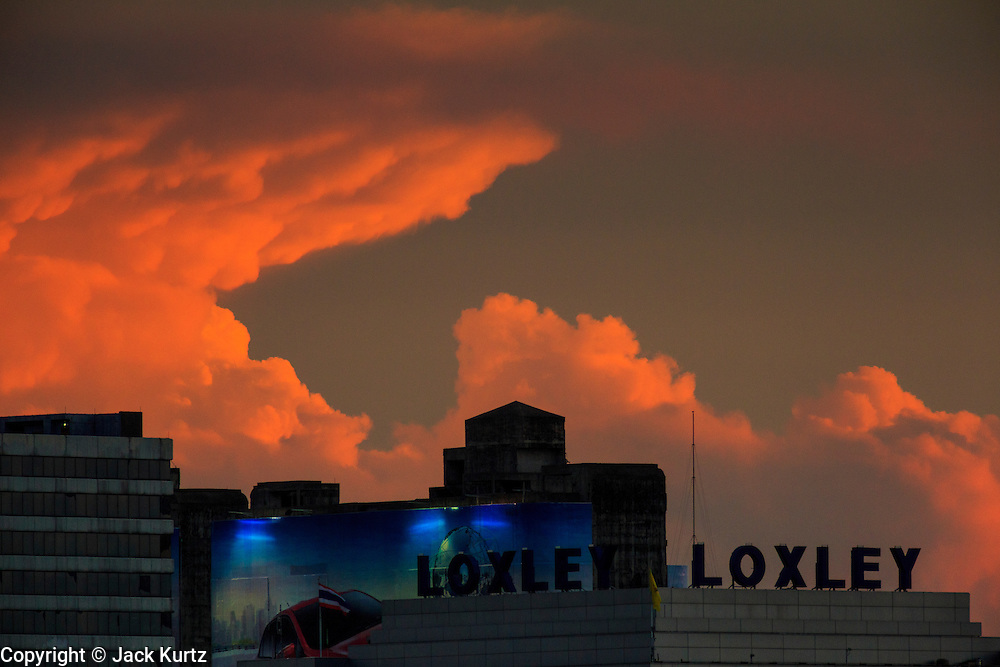 02 MAY 2013 - BANGKOK, THAILAND:   Clouds form at sunset over the corporate headquarters of Loxley, a Thailand-based company engaged in the trading and sale of information technology (IT) and telecommunication equipment in Bangkok, the capital of Thailand.    PHOTO BY JACK KURTZ