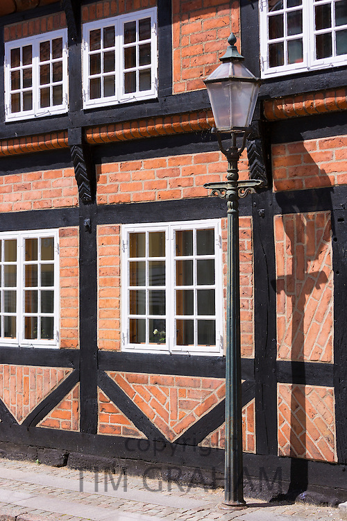 Old fashioned street lamp light and half-timbered house in Ribe centre, South Jutland, Denmark