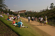 Spectators rest in the sun and admire the English garden flowers with the main Olympic stadium and basketball arena in the background during the London 2012 Olympics. London's Olympic Park, at just under a square mile, is the largest new park in the city for more than 100 years. The planting of 4,000 trees, 300,000 wetland plants and more than 150,000 perennial plants plus  nectar-rich wildflower make for a colourful setting for the Games. This land was transformed to become a 2.5 Sq Km sporting complex, once industrial businesses and now the venue of eight venues including the main arena, Aquatics Centre and Velodrome plus the athletes' Olympic Village. After the Olympics, the park is to be known as Queen Elizabeth Olympic Park.