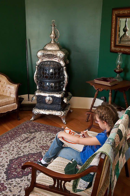 A young girl colors in the restored parlor of the St. Helena Island Lighthouse.