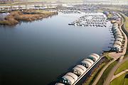 Nederland, Gelderland, Maasbommel, 11-02-2008; .floating houses in the river Maas; drijvende woningen in het water van recreatiegebied De Gouden Ham, onderdeel van de rivier de Maas (rivier geheel boven in beeld); de recreatiewoningen maken onderdeel uit van een complex van buitendijks gebouwde tweede huizen, die (gaan) drijven bij hoog water; de woningen zijn bevestigd aan meerpalen om verschillen in waterhoogte op te vangen; onder in beeld permanentn drijvende huizen, in het midden de amfbische huizen die alllen gaan drijven bij hoog water; jachthaven in de achtergrond; ruimte voor de rivier, wateroverlast, hoog water, waterhuishouding, waterbeheer, watermanagement, klimaatverandering, global warming, milieu, waterwoningen;..luchtfoto (toeslag); aerial photo (additional fee required); .foto Siebe Swart / photo Siebe Swart
