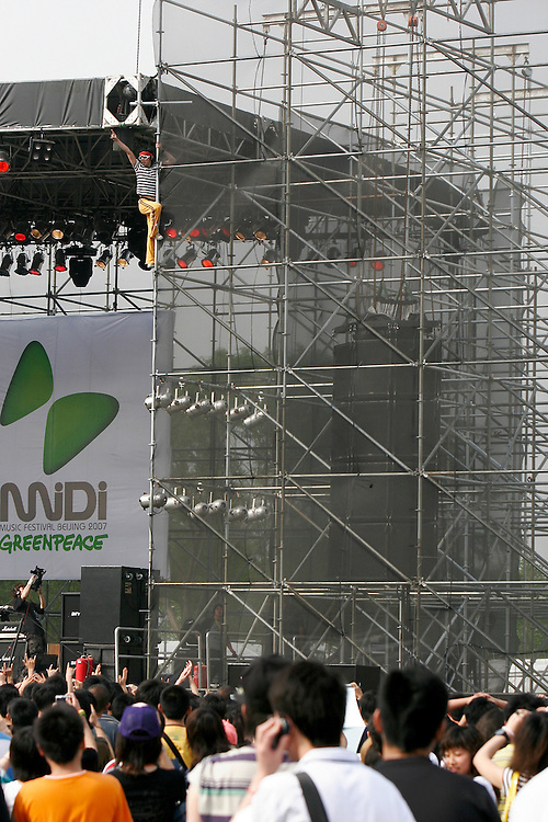 A performer climbs the stage scaffolding during the Midi Festival in Beijing China 2007. Midi is an alternative rock music festival held in northern Beijing catering to a small group of music listeners.  The festival lasts 4 days and gives performances from Chinese and international bands.