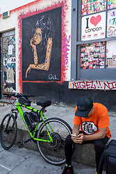 © Licensed to London News Pictures. 23/07/2021. LONDON, UK.  A delivery rider checks his phone in front of a mural of Amy Winehouse by street artist Otto Schade in Hawley Street in Camden Town on the tenth anniversary of the late singer's death.  Photo credit: Stephen Chung/LNP