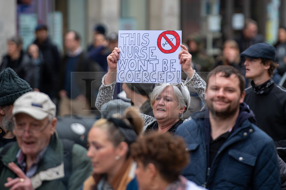 © Licensed to London News Pictures. 20/03/2021. London, UK. A woman holds up a placard as the crowd walks along Oxford Street during the anti-lockdown demonstration 'Worldwide Rally For Freedom' held in central London. Photo credit: Peter Manning/LNP