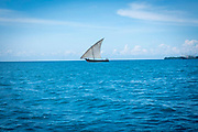 A small sail fishing boat on the sea between Stone Town and Changuu Island Zanzibar, Tanzania.