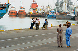 Iraqi workers on the dock side with ships and freighters in the background at Iraqs only port of Umm Qasr March 2005.