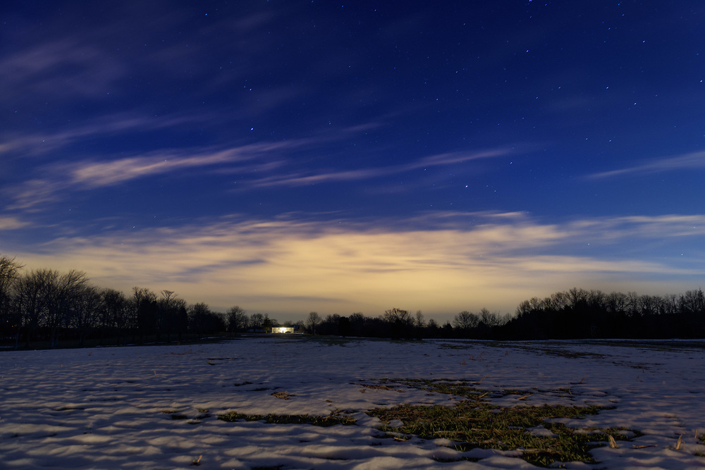 A lone house is seen in the distance of a snowy field under a starry sky. Taken on the side of River road somewhere between Edwards and Whites Ferry, West of the towns of Poolesville and Dickerson, Maryland.