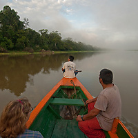 A small, motorized boat carries a tourist and Indian guides up the Yanayacu River in Peru's Amazon Jungle.