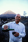 Mr Montrond serves a glass of wine produced in Cha das Caldeiras, a disperse village inside Fogo's volcano caldera. The rich volcanic soil helps the growing of vineyards and coffee plants. Despite the danger of living so close to the volcano the villagers rejected to move after the last eruption in 1995.
