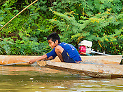 19 JUNE 2016 - DON KHONE, CHAMPASAK, LAOS:  A boy pulls in his fishing nets near Don Khone Island. Don Khone Island, one of the larger islands in the 4,000 Islands chain on the Mekong River in southern Laos. The island has become a backpacker hot spot, there are lots of guest houses and small restaurants on the north end of the island.     PHOTO BY JACK KURTZ