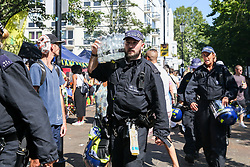 © Licensed to London News Pictures. 26/08/2019. London, UK. A police officer carries a case of drinking water on a very hot day as over a million people  take part in Notting Hill Carnival, Europe's largest street party and a celebration of Caribbean traditions and the capital's cultural diversity. Photo credit: Dinendra Haria/LNP
