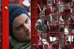 © licensed to London News Pictures. London, UK 14/02/2013. A man looking at heart-shaped name tags on a heart-shaped fence which marks Valentine's Day by The British Heart Foundation in Covent Garden, London. Photo credit: Tolga Akmen/LNP