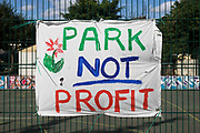 A Park Not Profit banner prepared by local residents and campaigners is displayed on fencing around sports facilities at Bells Gardens in Peckham on 14th August 2021 in London, United Kingdom. Southwark Council proposes to build 97 new homes a mix of social and private housing, a reprovisioned community facility and a multi-use games area at Bells Gardens, a well-used community park serving the 545-home Bells Gardens estate. Southwark ranks fifth-worst in London and eighth-worst in the UK for easy access to green space.