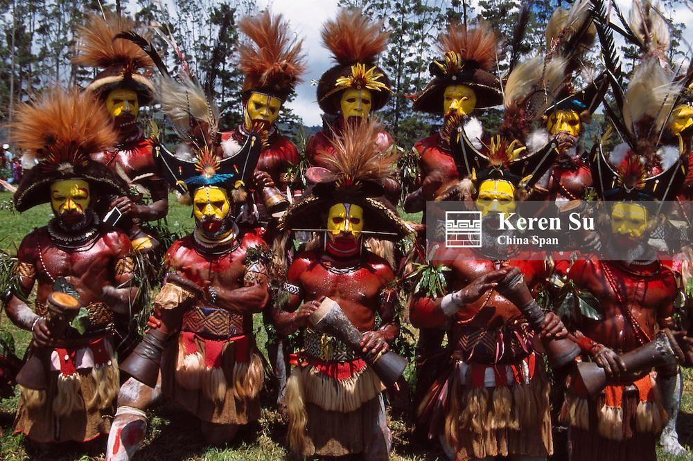 Huli wigmen beating kundu drum and dancing at Sing Sing Festival, Mt. Hagen, Papua New Guinea