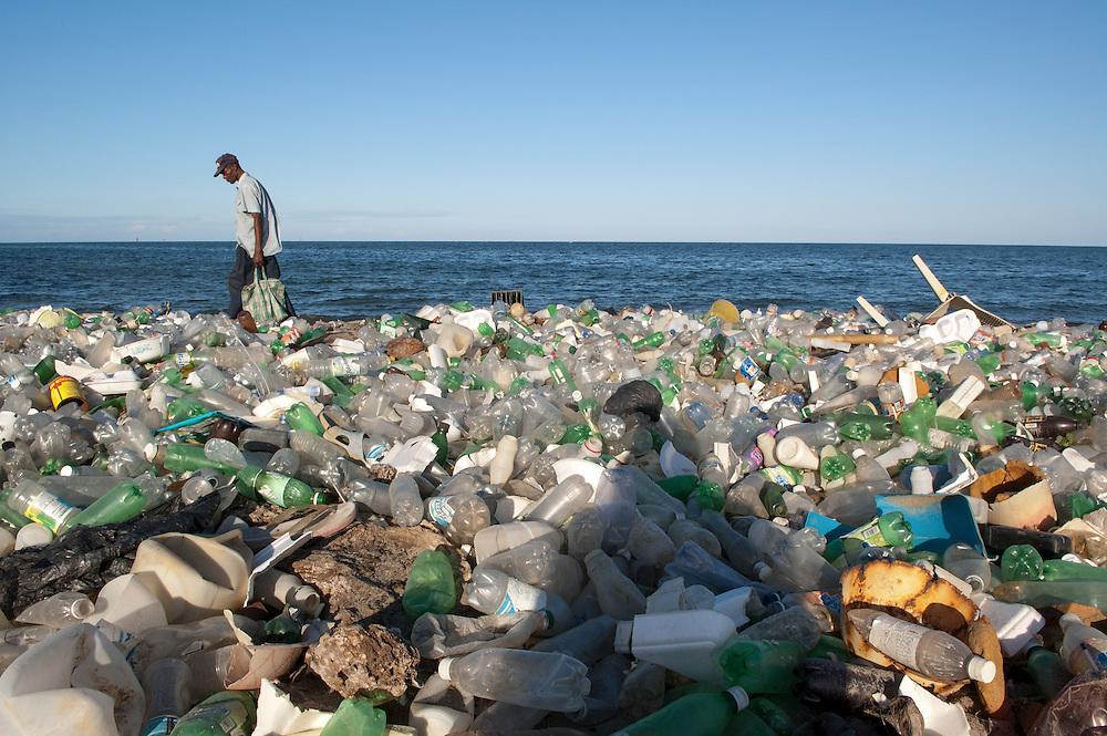 A Haitian man walks along a bottle-strewn part of the coastline surrounding Cap Haitian, Haiti. January 26, 2008.