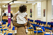A young father has a hug with his baby daughter during a family visit in HMP Brixton, South London on the 26th of July 2016, London United Kingdom. The Prisoner Advice & Care Trust (PACT) organise special family days that help the men inside the prison connect with and support their partners and children on the outside. (photo by Andy Aitchison)