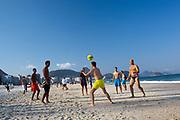 Brazilian men playing football on Copacabana beach, Rio de Janeiro.