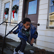 A young boy plays in the main street of Sandy Hook after yesterday's shootings at Sandy Hook Elementary School, Newtown, Connecticut, USA. 15th December 2012. Photo Tim Clayton
