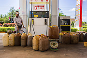 29 JUNE 2013 - PURSAT, CAMBODIA:  A gas station employee fills plastic cans with gasoline in a gas station near Pursat, about halfway between Phnom Penh and Battambang. The gas will be transferred to small bottles - usually recycled liquor and soft drink bottles - and then sold at road side stands to motorcyclists and tuk-tuk drivers.    PHOTO BY JACK KURTZ