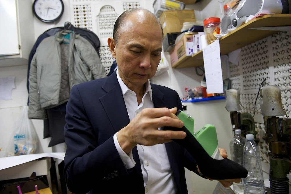 Fashion designer Jimmy Choo inspects a pair of bespoke shoes in his studio on Cannaught Street, London, March 22, 2010.