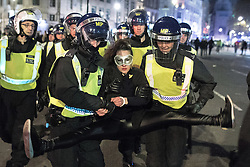 © Licensed to London News Pictures . 05/11/2016 . London , UK . Police detain , handcuff and carry away a woman from the protest in Trafalgar Square . Supporters of Anonymous , many wearing Guy Fawkes masks , attend the Million Mask March bonfire night demonstration , in central London . Photo credit : Joel Goodman/LNP