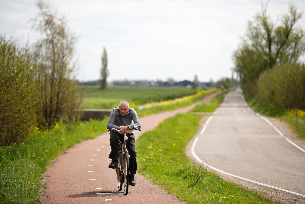 In Zegveld rijdt een eenzame fietser over het fietspad langs de weilanden.<br /> <br /> In Zegveld a lonely cyclist rides near the pastures.