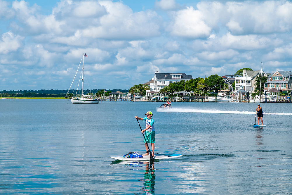 Paddleboards and jet skis at the soundside of Wrightsville Beach, North Carolina on Tuesday, August 10, 2021. Copyright 2021 Jason Barnette