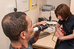 Homeless man having his lung capacity measured as part of an assessment for TB in central London
