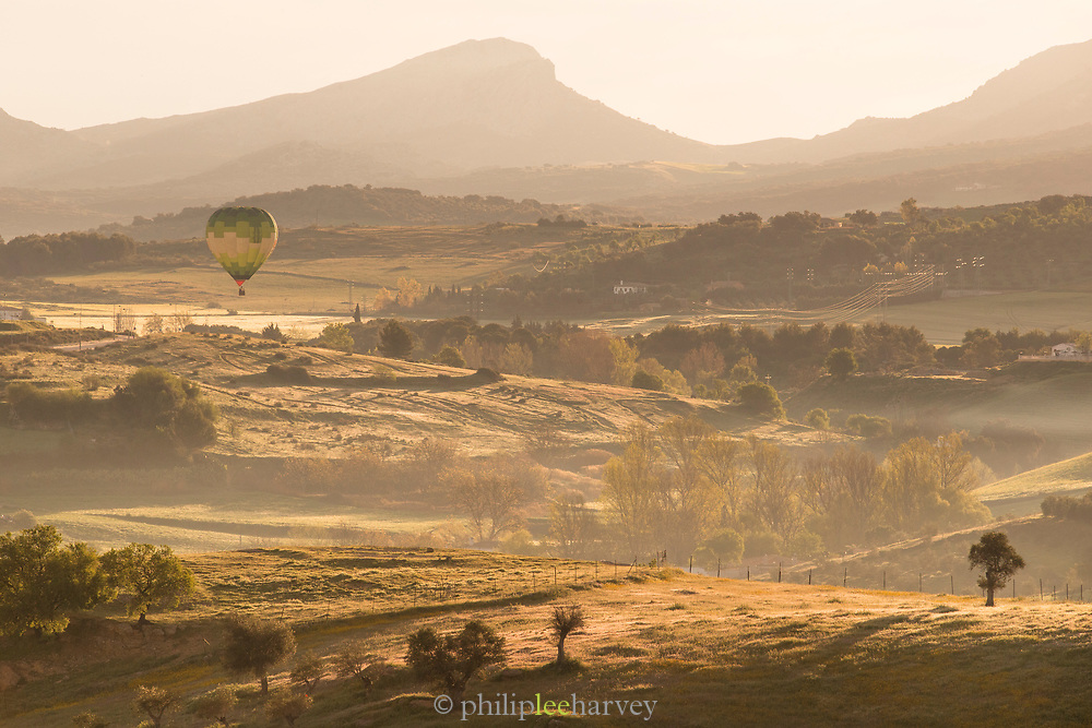 Hot air balloon flying over rolling landscape at sunrise, Ronda, Andalusia, Spain