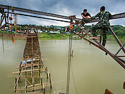 15 SEPTEMBER 2014 - SANGKHLA BURI, KANCHANABURI, THAILAND:  Thai army engineers work on a scaffolding on the Mon Bridge in Sangkhla Buri. The 2800 foot long (850 meters) Saphan Mon (Mon Bridge) spans the Song Kalia River. It is reportedly second longest wooden bridge in the world. The bridge was severely damaged during heavy rainfall in July 2013 when its 230 foot middle section  (70 meters) collapsed during flooding. Officially known as Uttamanusorn Bridge, the bridge has been used by people in Sangkhla Buri (also known as Sangkhlaburi) for 20 years. The bridge was was conceived by Luang Pho Uttama, the late abbot of of Wat Wang Wiwekaram, and was built by hand by Mon refugees from Myanmar (then Burma). The wooden bridge is one of the leading tourist attractions in Kanchanaburi province. The loss of the bridge has hurt the economy of the Mon community opposite Sangkhla Buri. The repair has taken far longer than expected. Thai Prime Minister General Prayuth Chan-ocha ordered an engineer unit of the Royal Thai Army to help the local Mon population repair the bridge. Local people said they hope the bridge is repaired by the end November, which is when the tourist season starts.   PHOTO BY JACK KURTZ