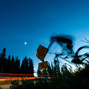 Jeff Brines rides the new Hightower LT from Santa Cruz Bicycles. On the Bootpack Trail off of Teton Pass. Crossing highway after dark with moon in sky.