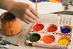 Secondary school student painting a picture in an art lesson,