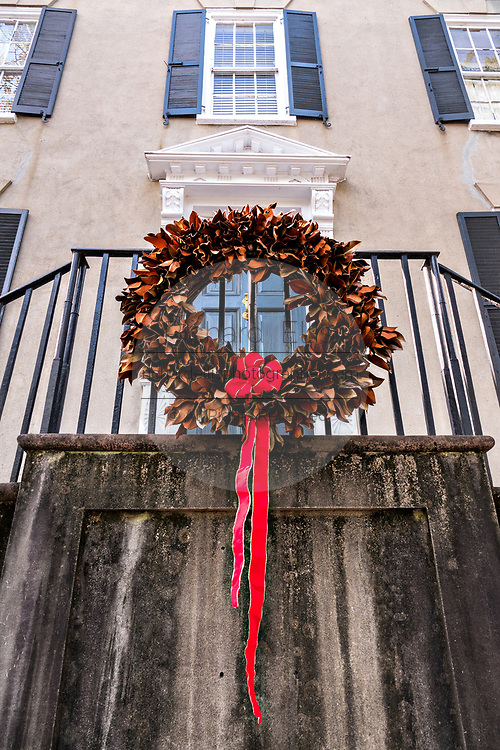 A magnolia Christmas wreath decorates a historic home at Meeting Street in Charleston, SC.