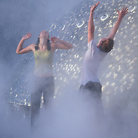 USA, Washington, Seattle, Soaked young couple plays at International Fountain at Seattle Center by Space Needle