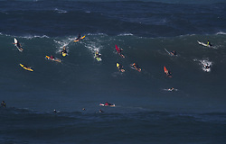 December 13, 2017 - Waimea Bay, HI, USA - WAIMEA BAY, HI - DECEMBER 13, 2017 - Professional surfer John John Florence of Hawaii, center (green board) paddles into a large wave at Waimea Bay. The big wave surfing spot only breaks in the winter when storms send large north swells toward the North Shore of Oahu. (Credit Image: © Erich Schlegel via ZUMA Wire)