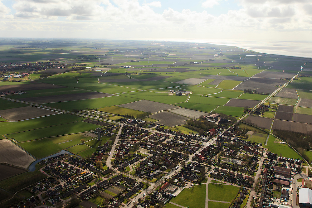 Nederland, Friesland, Het Bildt, 16-04-2012. Sint Jacobiparochie, gelegen midden tussen de zeekleipolders van Het Oud Bildt. Waddenzee aan de horizon..VIllage amidst polders, reclaimed from the Wadden sea (at the horizon)..luchtfoto (toeslag), aerial photo (additional fee required);.copyright foto/photo Siebe Swart
