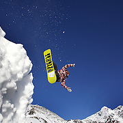A snowboarder takes to the air at The Remarkables Ski Fields, Queenstown, New Zealand during a session with 'The Air Bag'  a large inflatable airbag which breaks the fall of the participant on landing and allows valuable experience and a training aid for Aerial skiers and snowboarders. Queenstown, South Island, New Zealand, 18th July 2011