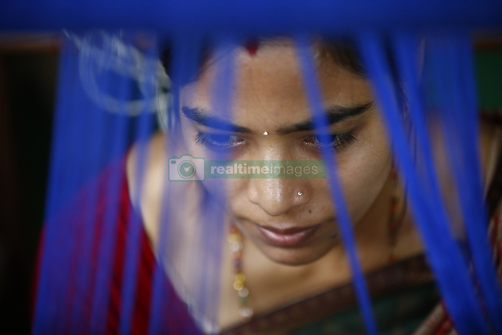 October 2, 2018 - Kathmandu, Nepal - A Nepalese woman who is victims of violence, abuse and poverty weaves fabrics at a textile production center in Kathmandu. The Production Center of Women's Foundation Nepal is situated in Boudha of the Capital.  There are more than 70 women aged above 45, who work to produce scarves, textiles and necklaces.  These women are producing and delivering around a total of 10-12kg materials per day.  Their basic income per month is between rupees 6,000-7,000 (Nepalese Currency) which comes around approximately 0-0. The handicrafts are sold in the center in a local price and are mainly exported to Europe, United States and Canada. The money from the exported items is used as charity to the women and children to cover all their basic needs, access provided to educational opportunities for the children, medical cost, psychological and legal assistance. The survivors of violence or abused children approximately 40-60 children aged 1-6 years go to kindergarten. Over 450 children from grade 1 to 10 studies at a school near Boudha.  The Women's Foundation Nepal also provides a safe shelter home for the young girls, boys and mothers. The shelter home has more than 120 children and 30 women and the above-mentioned expenditure is all funded by WFN. (Credit Image: © Skanda Gautam/ZUMA Wire)
