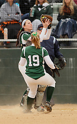 30 March 2013:  Katie Crane pulls in a popped up ball in front of Chloe Montgomery during an NCAA Division III women's softball game between the DePauw Tigers and the Illinois Wesleyan Titans in Bloomington IL<br /> <br /> Umpire is Jay MacDaniels of Pekin IL