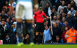 Referee Graham Scott inspects the broken corner flag during the FA Cup fourth round match at Etihad Stadium, Manchester.